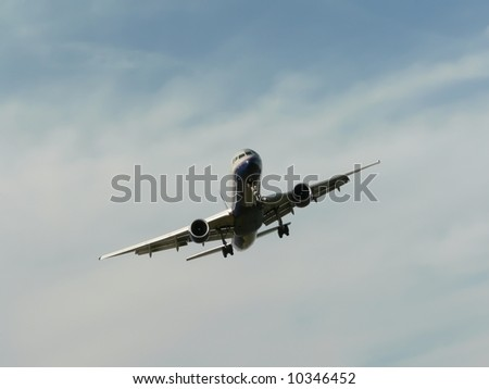 commercial jet in flight with landing gear exposed