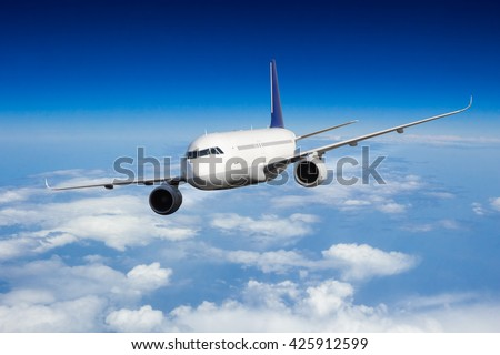 Commercial jet plane flying above clouds in day light - stock photo