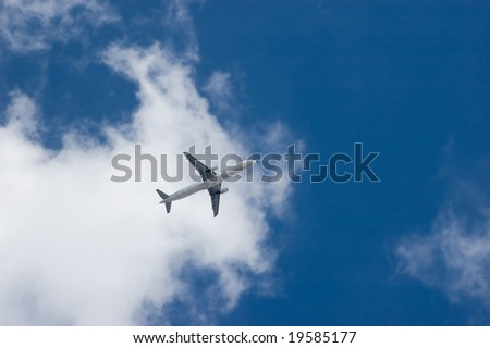Commercial jet plane flying in the sky among clouds - stock photo