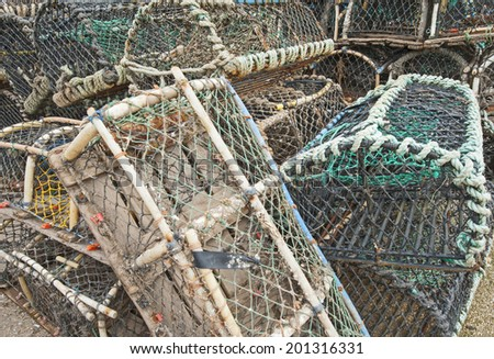 Commercial lobster fishing pots stacked on quayside of a fishing port - stock photo