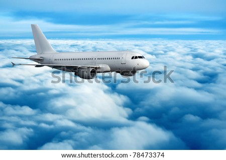 commercial passenger airplane flying over clouds