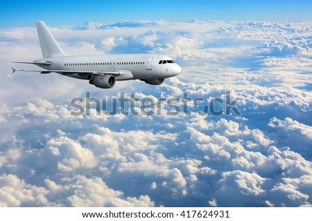 Commercial passenger plane flying above clouds - stock photo