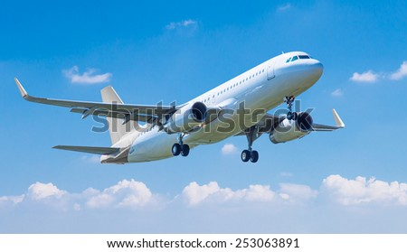 Commercial plane taking off against blue sky - stock photo