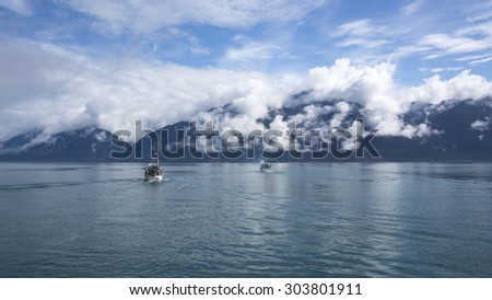 Commercial salmon fishing boats heading out to fish in the Lynn Canal near Haines Alaska. - stock photo