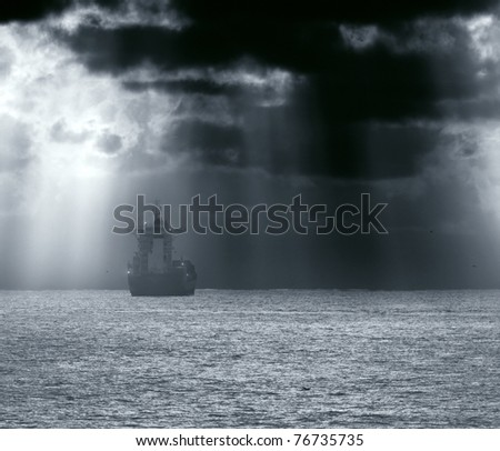 Commercial Ship crossing ocean in a stormy sunset with sun beams; enhanced sky - stock photo