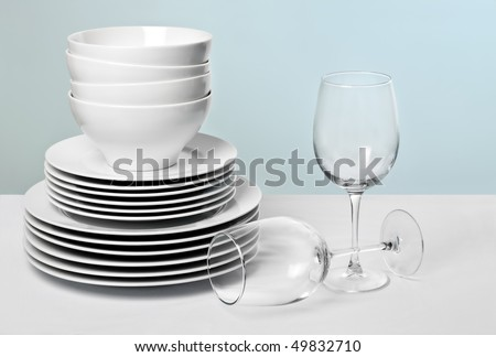 Commercial white plates and bowls stacked with crystal wine glasses - stock photo