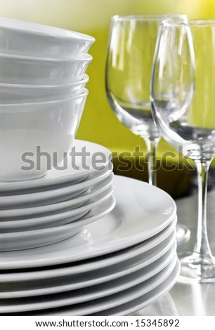 Commercial white plates bowls with blurred wine glasses against green background - stock photo
