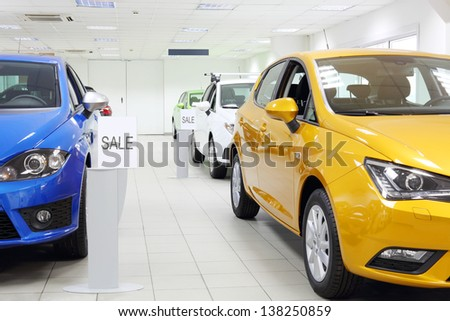Commercially colourful shining cars stand in light car shop. - stock photo
