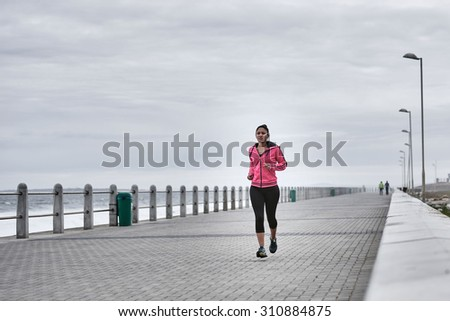 Committed female runner is dedicated to taking her morning run every morning as part of her daily routine to promote fitness - stock photo