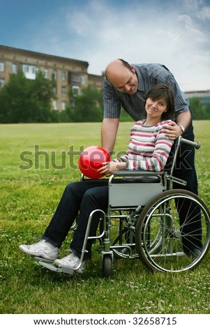 Committed helper care about friend in wheelchair - stock photo