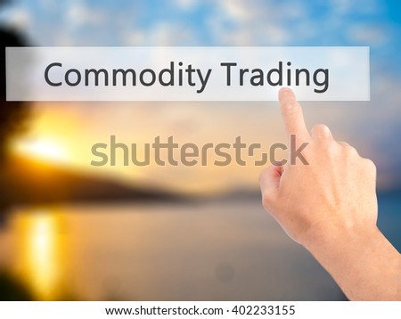 Commodity Trading - Hand pressing a button on blurred background concept . Business, technology, internet concept. Stock Photo