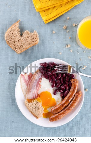 Common breakfast on a white plate: bacon, fried egg, red beans and sausage. Meal is served on a table on a light blue tablecloth. Taken  directly from above. - stock photo