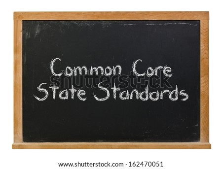 Common Core State Standards written in white chalk on a black chalkboard isolated on white - stock photo
