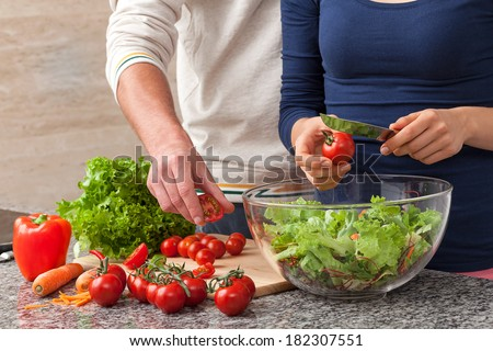 Common making a salad with fresh vegetables - stock photo