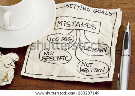 common mistakes in setting goals (too many, too big, not specific, not written) - a sketch drawing on a cocktail napkin with a coffee cup - stock photo
