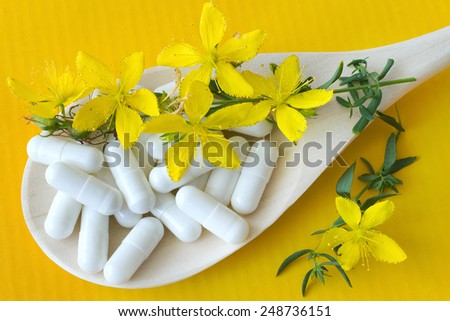 common St. John's wort -  hypericum perforatum - natural antidepressants - pill and yellow flowers with leaves - stock photo