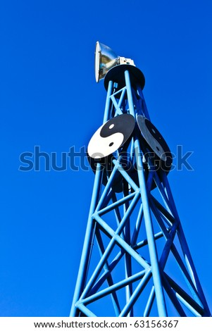 Communication antenna tower against blue sky.