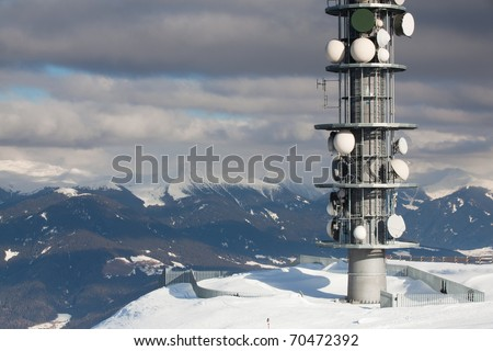 Communication antenna tower and satellite dishes against blue sky. - stock photo