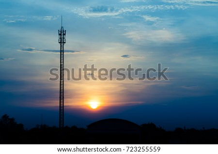 Communication base antenna with twilight in evening sky and blurred focus for background silhouet