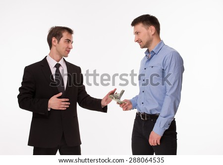 Communication between two men about bribery. Man in blue shirt giving money to man in brown business suit. - stock photo