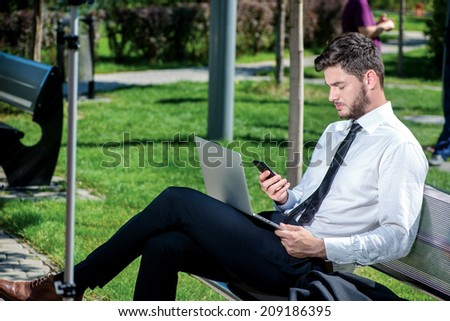 Communication by mobile phone. Confident and successful businessman holding a mobile phone and waits for a call from the client. Successful businessman in formal attire.