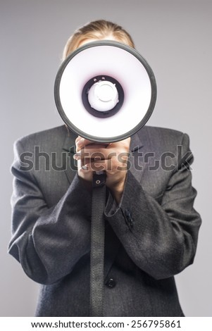 Communication Concept: blond Female Holding Big White Megaphone Against Face. Vertical Image