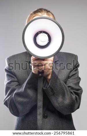 Communication Concept: blond Female Holding Big White Megaphone Against Face. Vertical Image - stock photo