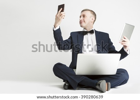 Communication Concept. Handsome Caucasian Man in Suit Using Digital Pad, Smartphone and Laptop for Multiple Communication. Horizontal  Image Orientation - stock photo