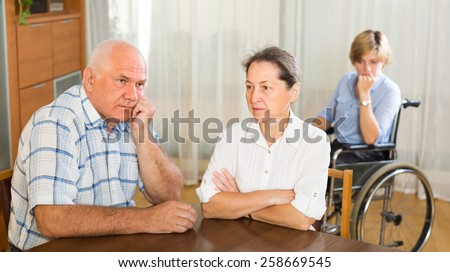 Communication problems between woman in wheelchair and mature relative. Focus on woman - stock photo