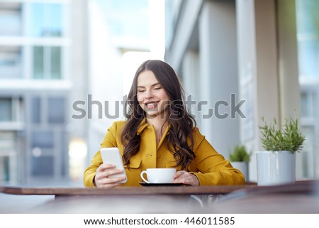 communication, technology, leisure and people concept - happy young woman or teenage girl texting on smartphone and drinking cocoa at city street cafe terrace - stock photo