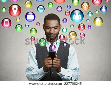 communication technology mobile phone high tech concept. business man using texting on smartphone social media application icons flying out of cellphone isolated grey wall background. 4g data plan  - stock photo