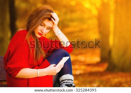 Communication technology. Sad upset girl unhappy woman sitting on bench in autumn park with mobile phone smartphone, reading sms - stock photo