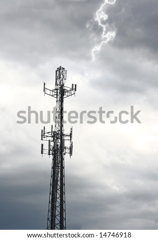 Communication tower against gray cloudy sky