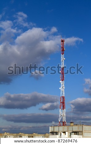 Communication tower near high-rise building with a large number of antennas installed - stock photo