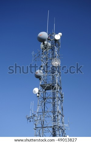 Communication tower over a deep blue sky. - stock photo