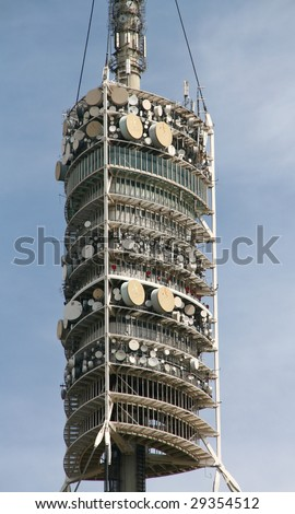 communication tower with antennas and dishes - stock photo