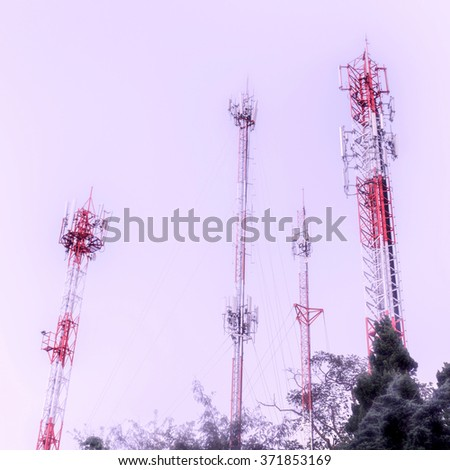 Communication towers over misty cloud sky in rural areas - stock photo
