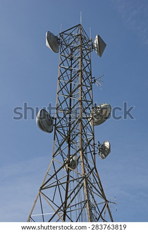 communications antenna tower with parabolic dish and other aerials - stock photo