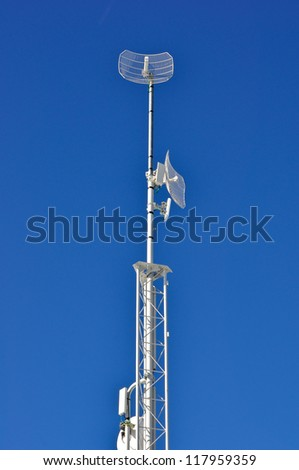 Communications tower against a blue sky.
