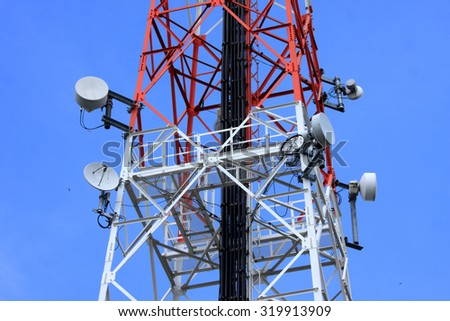 communications tower and satellite on blue sky - stock photo