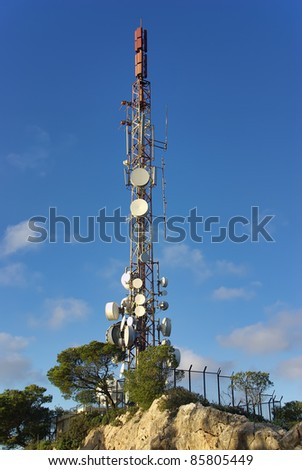 Communications tower on a mountain with a lot of antennas installed - stock photo