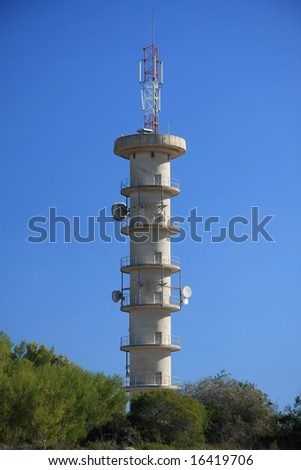 Communications tower with antennae and dishes against blue sky