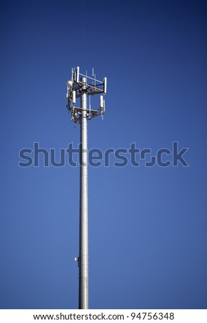Communications tower with antennas against blue sky. - stock photo