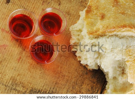 Communion bread and wine on a rustic surface. - stock photo