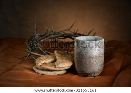 Communion cup and bread with crown of thorns in background - stock photo