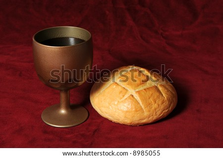 Communion elements represented by bread and wine over a red background - stock photo