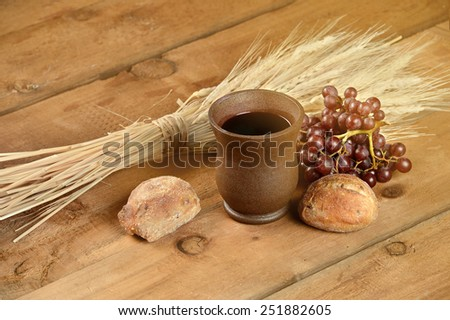 Communion elements with wine, bread, wheat, grapes and cup on vintage table with sunlight flair effect - stock photo