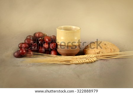 Communion table with cup of wine, grapes, bread and wheat - stock photo