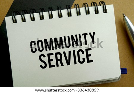 Community service memo written on a notebook with pen