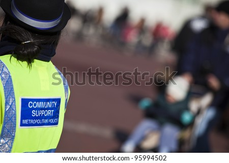 Community support police officer on duty. Daytime in public place outdoor - stock photo